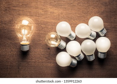 Bigger light bulb glowing out of the group of small light bulbs, influence leader and follower idea
