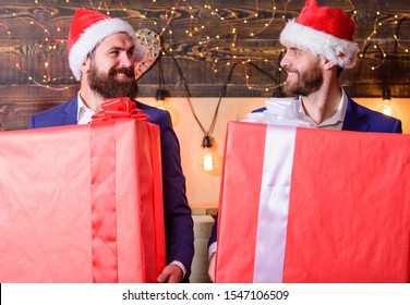 Biggest gift for christmas. Big wrapped box with ribbon. Great surprise. Prepare huge surprise gift. Men compete who has larger size. Bigger gift battle. Men santa carry big gift boxes. Size matters.