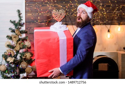 Biggest gift for christmas. Celebrate christmas with giant gifts. Big wrapped box with ribbon. Great surprise. Prepare huge surprise gift. Man santa claus hat carry big gift box. Size matters.