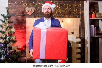 Biggest gift for christmas. Size matters. Celebrate christmas with giant gifts. Big wrapped box with ribbon. Great surprise. Prepare huge surprise gift. Man santa claus hat carry big gift box.
