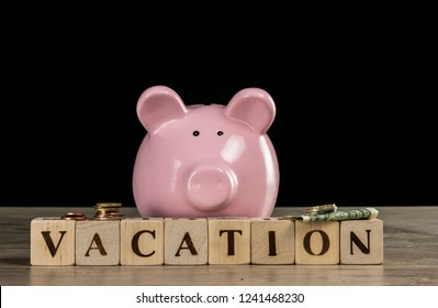 Biggy bank and letter cubes forming the word vacation