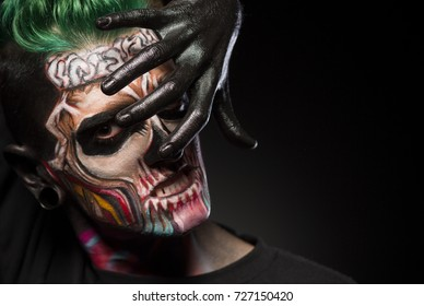 Bight makeup for Halloween party. Mans face with colored skull makeup, covering face with hand painted in black.