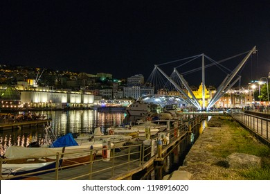 Bigo by Renzo Piano at night. Parked boats and people walking in the city. Porto Antico, Genoa, Italy