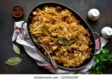 Bigos - cabbage stewed with meat, dried mushrooms and sausage in a skillet on a dark slate, stone or concrete background.Traditional dish of polish cuisine.Top view with copy space.