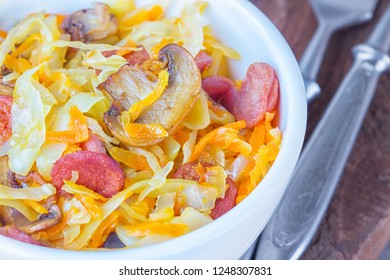 Bigos - stewed cabbage with carrots , smoked sausages and mushrooms, traditional dish of polish cuisine. Top view. Closeup.