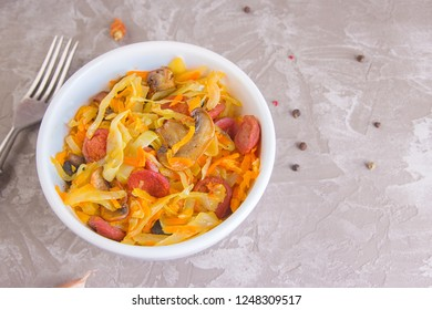 Bigos - stewed cabbage with carrots , smoked sausages and mushrooms, traditional dish of polish cuisine. Top view with copy space.