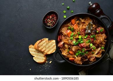 Bigos - plat traditionnel de cuisine polonaise, chou rôti de viande, saucisses et champignons séchés dans une poêle sur fond noir, pierre ou béton. Vue de dessus avec espace de copie.
