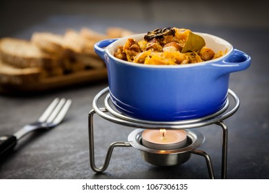 Bigos - a traditional Polish dish with sauerkraut and fresh cabbage with meat, bacon and mushrooms in blue ceramic pot on the steel food warmer