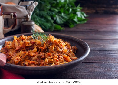 Bigos, a traditional Polish dish with sauerkraut and fresh cabbage with meat, sausage, ham and prunes, horizontal, copy space