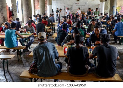 Bihac, BiH, July 07th 2018, Refugees eating meal in camp. Food distribution for hungry migrants. People standing in line and waiting for food in migrant shelter. Balkan Route. European migrant crisis