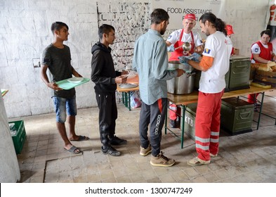 Bihac, BiH, July 07th 2018, Refugees eating meal in camp. Food distribution for hungry migrants. People standing in line and waiting for food in migrant shelter. Balkan Route. Food line. Bosnia. Syria