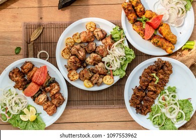Bihari kabab,malai boti,gola kabab and chicken tikka on a wooden table top  , top view . Traditional different types of BBQ