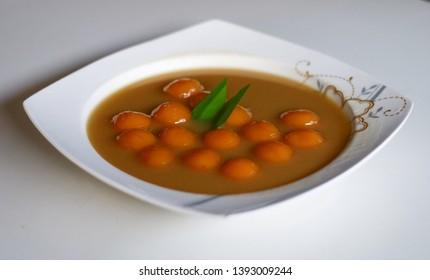 Biji salak on white background. Biji salak is sweet potato dumplings with coconut sauce. Popular dessert in Indonesia or to break the fast.