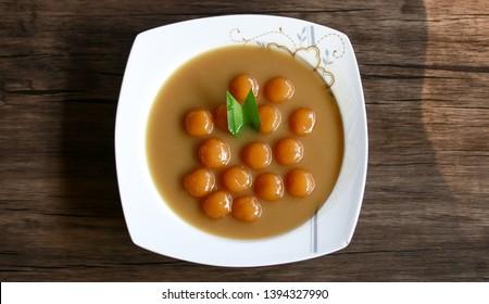 Biji salak on wood background. Biji salak is sweet potato dumplings with coconut sauce. Popular dessert in Indonesia or to break the fast.