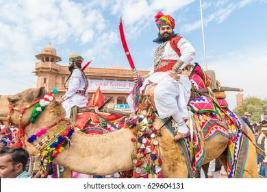 Bikaner, India, 14th January 2017 -  A Rajasthani man brandishing a sword atop of a camel at the Bikaner Camel Mela in Rajastan, India.