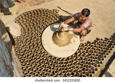 Bikaner, India - February 12, 2019: Indian potter making clay pots on pottery wheel in Bikaner. Rajasthan