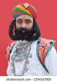 BIKANER, INDIA - JANUARY 12, 2019: Indian man with long mustaches poses for a photo during Camel Festival in Rajasthan