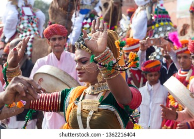 BIKANER, INDIA - JANUARY 12, 2019: Indian girl in traditional clothes dancing at festival in Rajasthan state. The Camel Festival begins with a colourful procession of camels, musicians and dancers