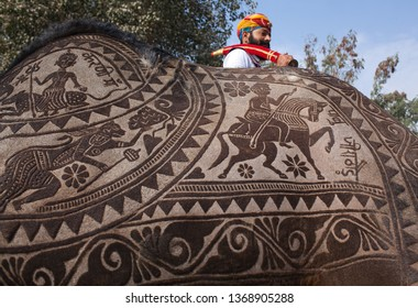 BIKANER, INDIA - JANUARY 12, 2019: Indian Rajasthani man in traditional clothes riding on camel during festival in Rajasthan state