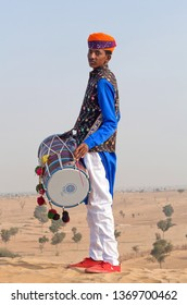 BIKANER, INDIA - JANUARY 12, 2019: Indian drummer in traditional clothes performing during Camel festival in Thar desert in Rajasthan state.