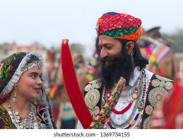 BIKANER, INDIA - JANUARY 12, 2019: Indian Rajasthani couple in national clothes poses for a photo during Camel Festival in Rajasthan