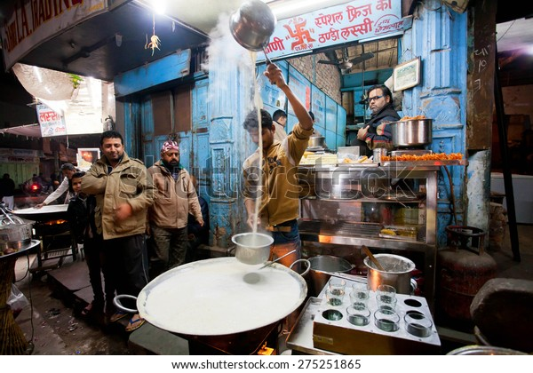BIKANER, INDIA - MAR 4: Young chef cooks milk with saffron near the street restaurant on March 4, 2015 in Rajasthan. Bikaner has population near 650,000. It was founded by maharajah Rao Bika in 1486