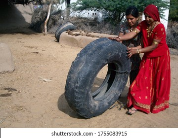 Bikaner, Rajasthan / India - January 12,2009: Two Rajasthani beautiful young girls carrying big tires in Ladera village of Bikaner