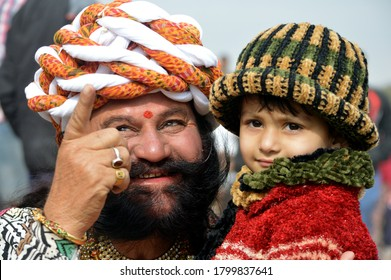 Bikaner, Rajasthan / India - January 13,2017: A little beautiful girl, turban and beard-mustard Rajasthani beautiful young man playing in the dock at Karni Singh Stadium Bikaner at the Camel Fair.