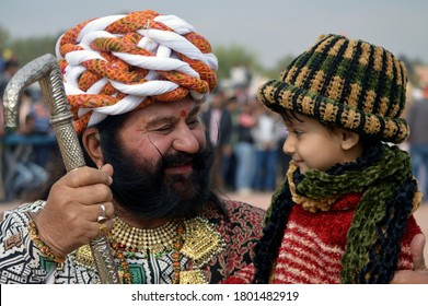 Bikaner, Rajasthan / India - January 13,2017: A little beautiful girl, turban and beard-mustard Rajasthani beautiful man playing in the dock at Karni Singh Stadium Bikaner at the Camel Fair.