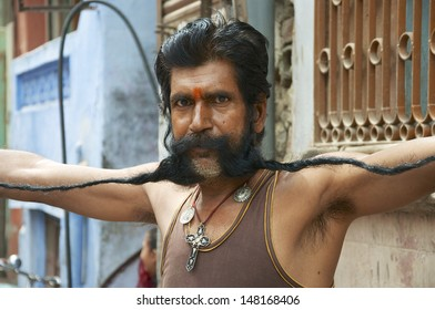 BIKANER, RAJASTHAN, INDIA - MARCH 27: Unidentified man unfurls and shows off his very long moustache on March 27, 2012. Growing long moustaches is popular in Rajasthan, competitions are often held.
