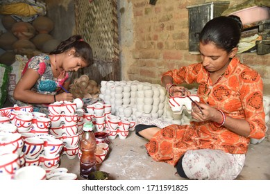 Bikaner, Rajasthan / India, October,19,2019 : Two young girls painted clay cups in traditional dress in the house of Gangahar, Bikaner