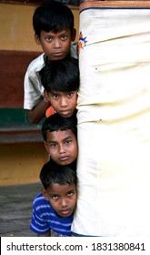 Bikaner, Rajasthan / India - September 18, 2012: Four beautiful children standing on the porch in Bikaner peeping behind the curtain