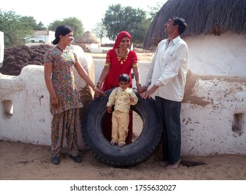 Bikaner, Rajasthan / India-January 12,2009: Young people peeping from inside big tires in Ladra village of Bikaner and two beautiful Rajasthani young girls and a child standing on either side