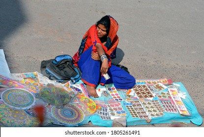 Bikaner, Rajsthan / India - November 02, 2013: Beautiful young woman wearing Rajasthani jewelery and costumes,selling worship materials for Indian Festival Diwali at Bikaner main market  on road