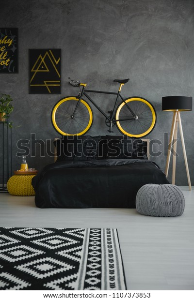 Bike above black bed in modern grey bedroom interior with patterned carpet, pouf and lamp. Real photo