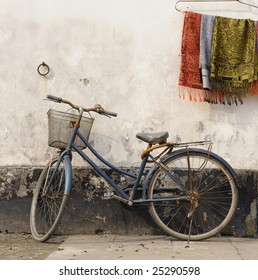 Bike against a wall at sunset in a hutong inside Suzhou,China.Next to the bike are hanging some colorful neckerchiefs