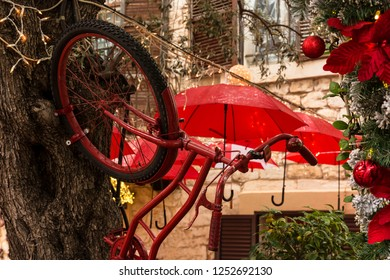 The bike is attached to a tree trunk against the background of red umbrellas and Christmas decorations.