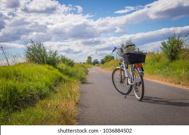 Bike with a basket in the middle of a rural asphalt road with a beautiful clouded sky