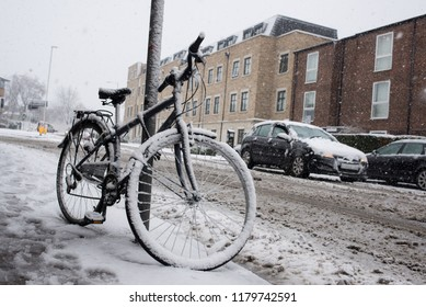 Bike covered in snow and frozen with busy traffic road in background during heavy snowing in Cambridge, England.