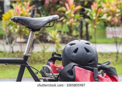 bike helmet on the rack bag  of bicycle, pannier, touring bike parking side of road