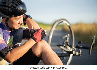 Bike injuries. Man cyclist fell off road bike while cycling. Bicycle accident, injured elbow.