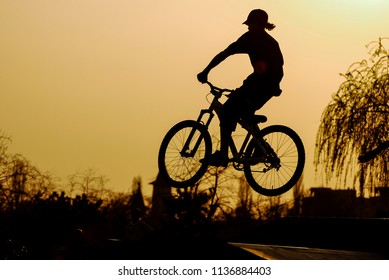 Bike jumps/Silhouette of a jumping biker on a mountain bike in an outdoor park projected against the sunset orange sky. Bucharest, Romania, April 5, 2009.