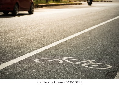 bike lane with car and motorcycle on background in evening sunlight