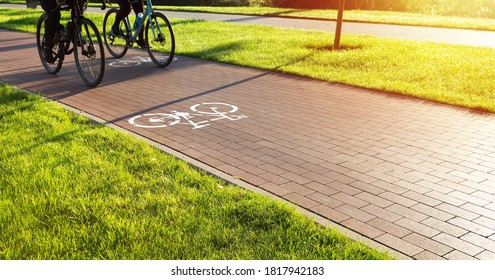 Bike lane in the city public park. Two cyclists ride the bike path early in the morning. Healthcare and active lifestyle.