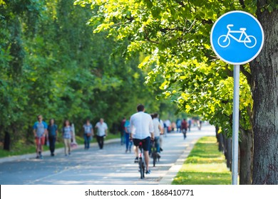 Bike lane, bike path sign in summer green park. Cyclists on bicycles and pedestrians. Concept of rest and relaxation, exercise, healthy lifestyle