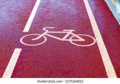 Bike lane with road symbol painting on red asphalt