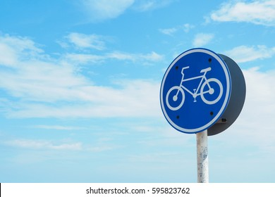 bike lane sign on a pole by the road with clear blue sky with clouds