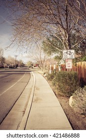 Bike Lane sign in a typical U.S. middle class neighborhood subdivision with a sidewalk.