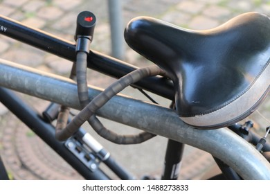 Bike locked to a metal bicycle stand. Closeup of saddle and bicycle lock.