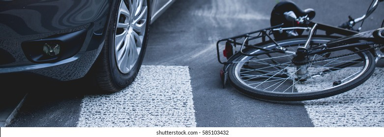 A bike lying on a street next to a car after accident, panorama